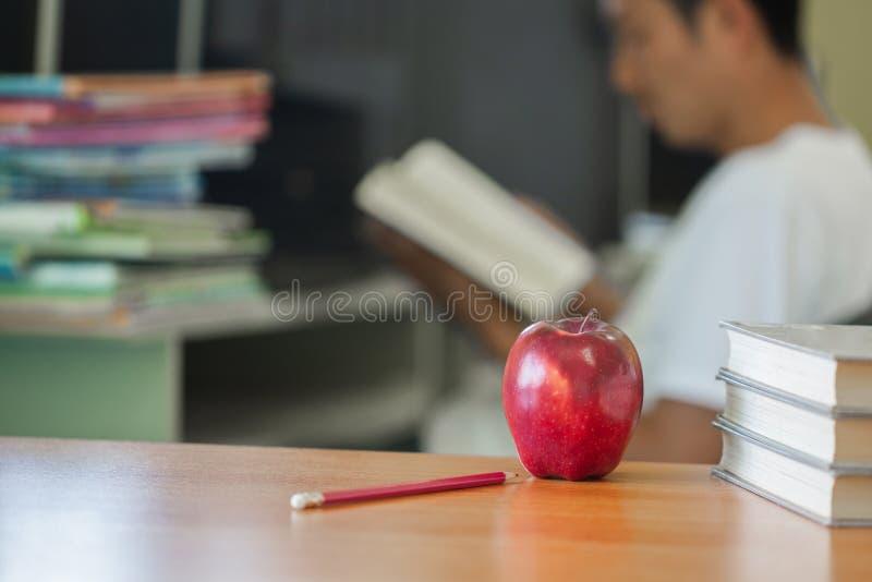 De school als thema had beeld bestaand uit een appel en uit een stapel van boeken de achtergrond een mensenzitting lezend een boe royalty-vrije stock fotografie