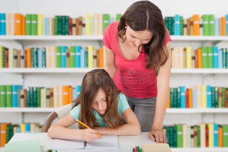 De Schoolbibliotheek van leraarsassisting girl at stock foto's
