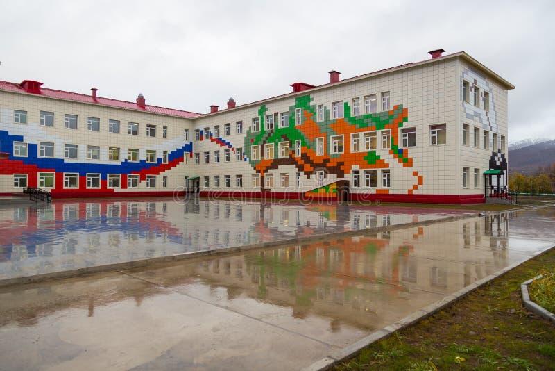De schoolbouw buiten met speelplaats, Esso, Kamchatka, Schiereiland stock foto's