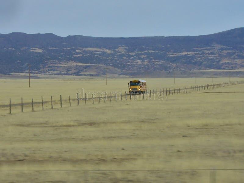 De schoolbus van de V.S. op een lange weg stock fotografie