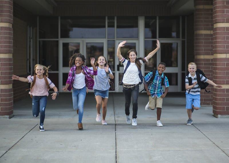De schooljonge geitjes die van de groepsschool aangezien zij het schoolgebouw verlaten lopen royalty-vrije stock foto's