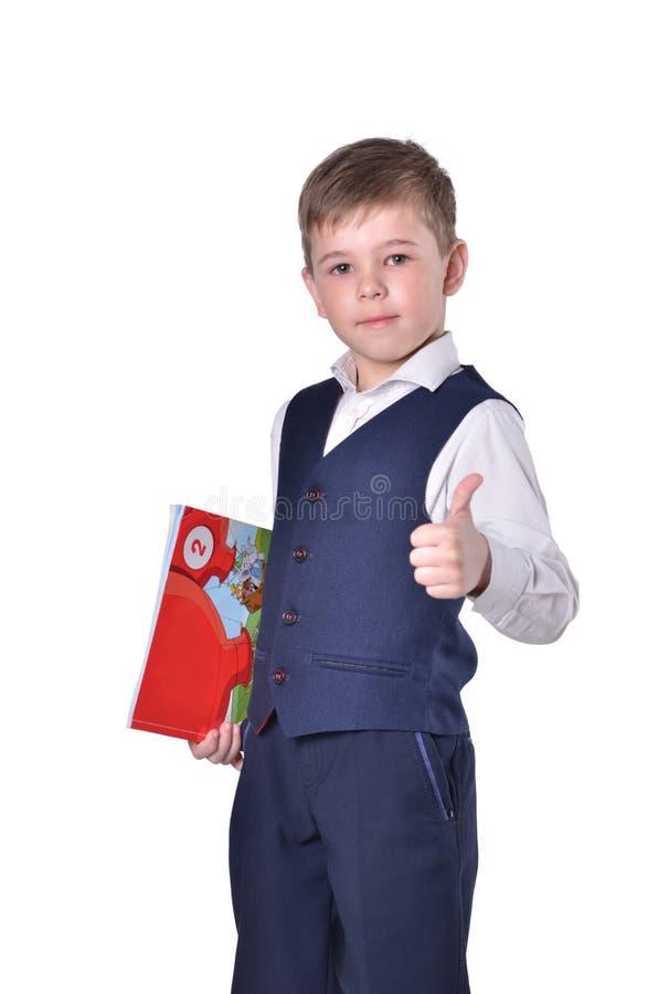 De schooljongen in blauw kostuum met boek in zijn hand beduimelt omhoog royalty-vrije stock foto's