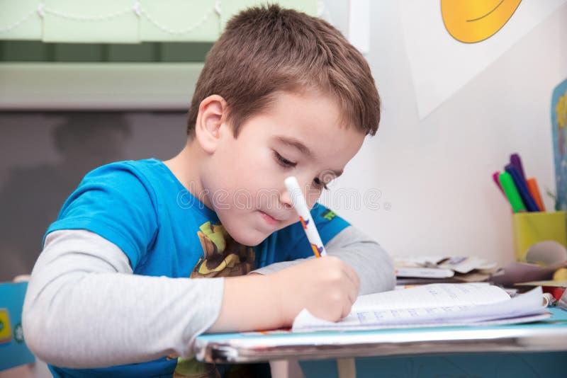 De schooljongen gebruikt pen aan praktijk thuis schrijvend op een notitieboekje bij zijn bureau royalty-vrije stock foto's
