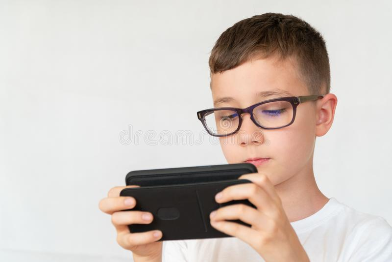 De schooljongen kijkt knappe smartphonevideo, in glazen royalty-vrije stock afbeelding