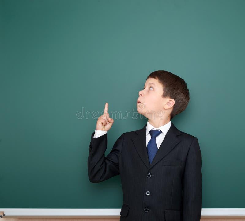 De schooljongen in zwart kostuum toont vinger op gebaar en is benieuwd, richt op groene bordachtergrond, onderwijsconcept royalty-vrije stock fotografie