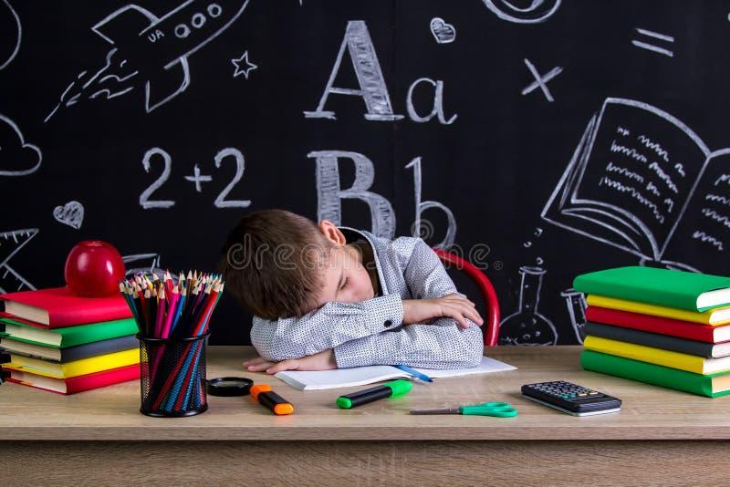 De schooljongenslaap bij het bureau met een hoofd leunde op de handen, met schoollevering die worden omringd Bord als a royalty-vrije stock foto's