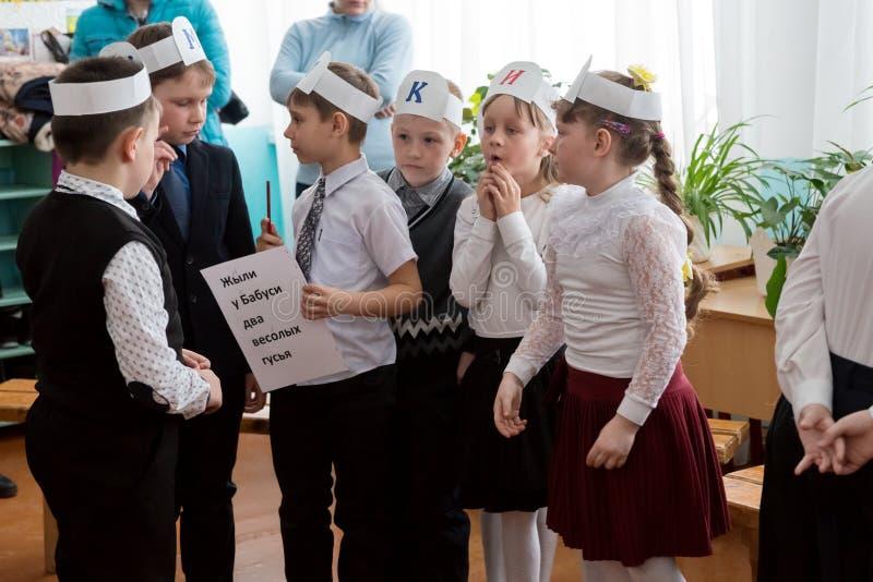 De schoolkinderen beslissen samen taak tijdens de spel thematische les in landelijke lage school, erachter zijn ouders stock afbeeldingen