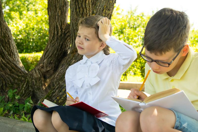 De schoolkinderen die thuiswerk, in het park in de verse lucht doen, het meisje dachten over de taak en krast haar hoofd stock afbeelding