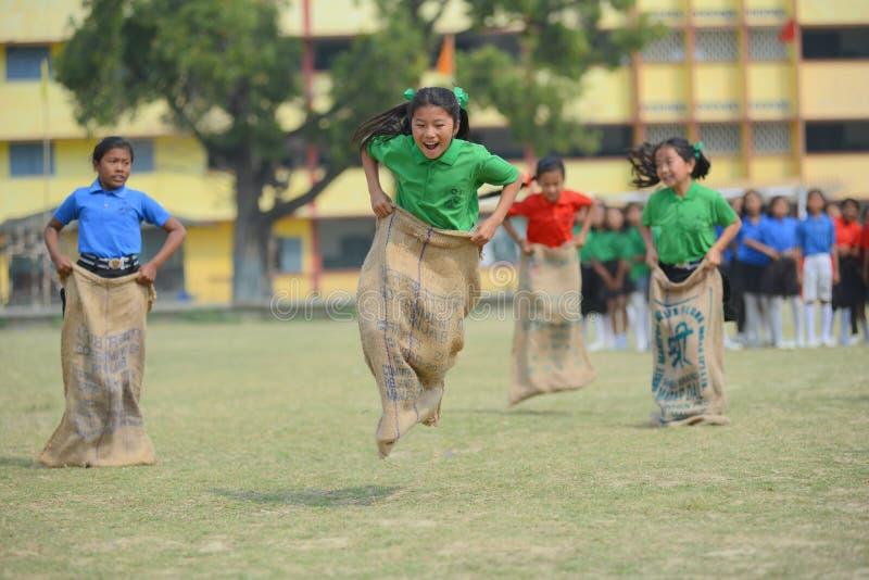 De schoolkinderen die in zak concurreren rennen royalty-vrije stock fotografie