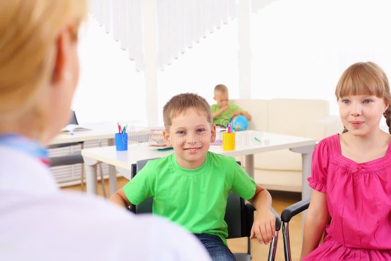 De schoolkinderen luisteren aan hun leraar royalty-vrije stock foto's