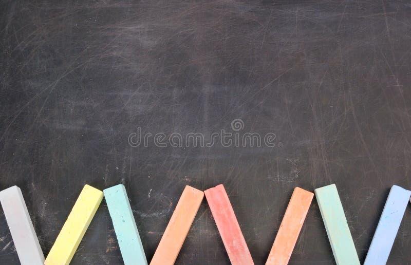 De schoolkrijt van de kleur op een zwarte raad stock afbeeldingen