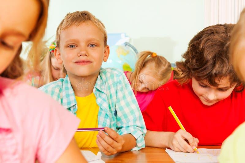 De schoolmakkers zitten samen in klaslokaal en schrijven royalty-vrije stock afbeeldingen