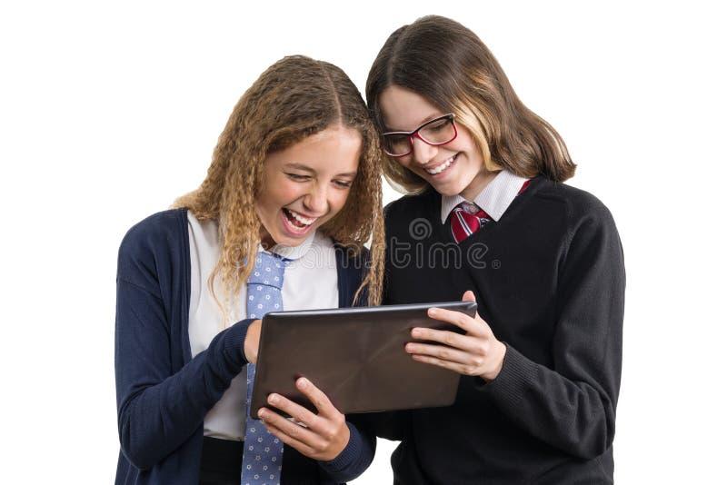 De schoolmeisjes bekijken de tablet De tieners in school eenvormig op witte achtergrond, beeld is geïsoleerd royalty-vrije stock fotografie