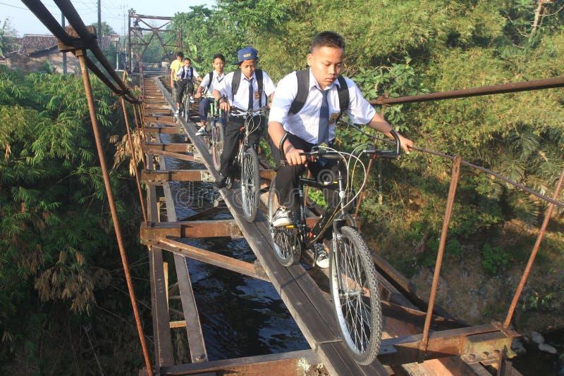 De schoolstudenten gaan naar school door de hangbrug royalty-vrije stock foto