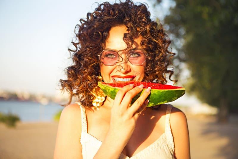 De schoonheid die krullende vrouw glimlachen draagt roze zonnebril en eet watermeloen stock fotografie