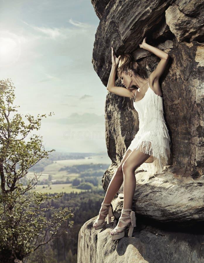 De schoonheid van de blonde het stellen op een gevaarlijke rots royalty-vrije stock afbeelding