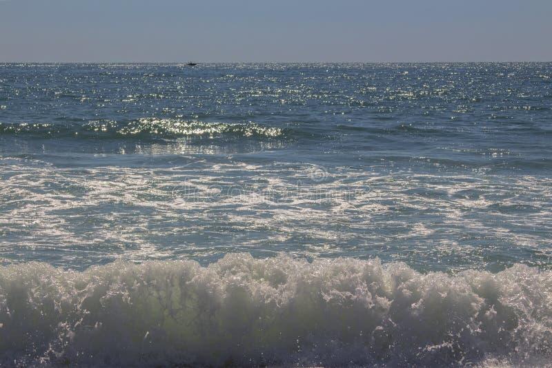 De schoonheid van de woedende overzeese golven Met de boot op de horizon stock fotografie