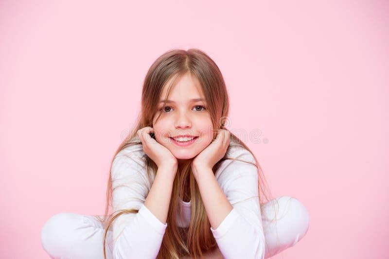 De schoonheid ziet en haarverzorging, punchy pastelkleur eruit De roze achtergrond van de meisjeglimlach Gelukkig kind met leuk g stock foto