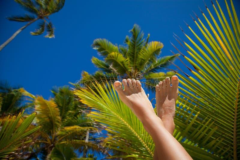 De schoonheidsbenen van de vrouw met manierpedicure bij strand stock afbeeldingen