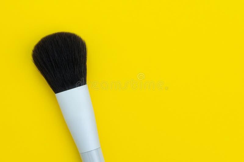 De schoonheidsborstel of maakt omhoog borstel want de dame op stevige gele achtergrond met exemplaar het ruimte gebruiken als man royalty-vrije stock afbeelding