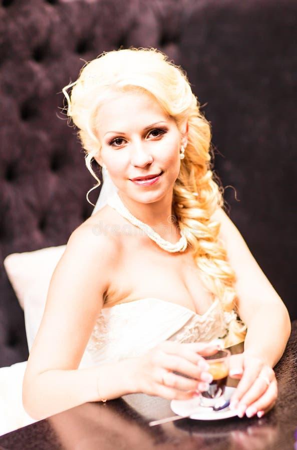 De schoonheidsbruid in bruids toga drinkt binnen thee Mooi modelmeisje in een witte huwelijkskleding Vrouwelijk portret van royalty-vrije stock foto