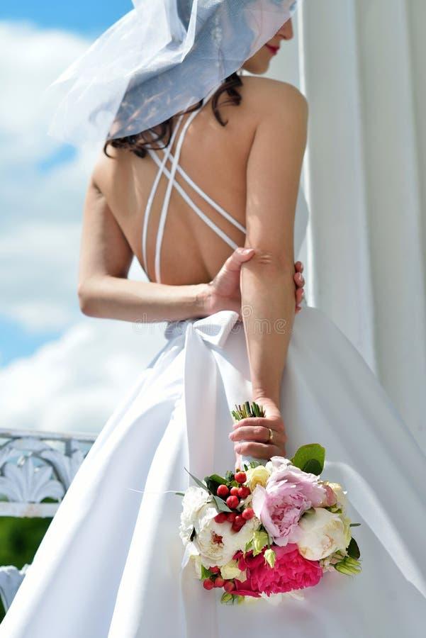 De schoonheidsbruid in bruids toga met boeket en het kant versluieren in de aard royalty-vrije stock afbeeldingen