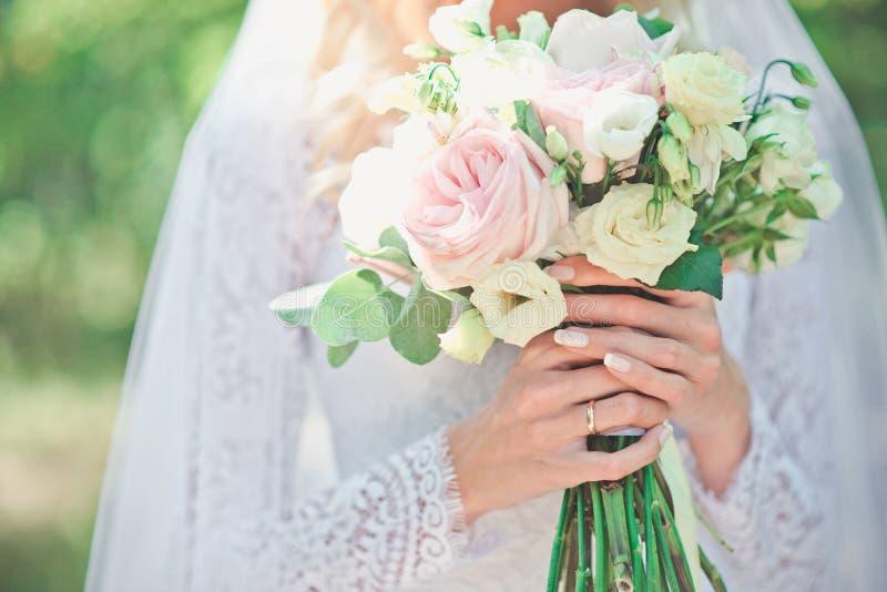 De schoonheidsbruid in bruids toga met boeket en het kant versluieren op de aard Mooi modelmeisje in een witte huwelijkskleding royalty-vrije stock foto's