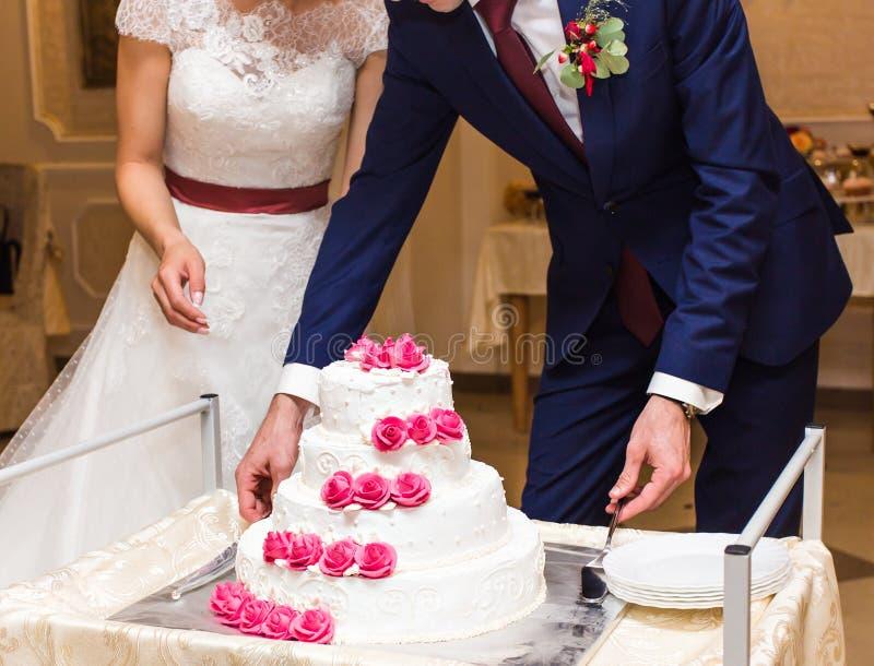 De schoonheidsbruid en de knappe bruidegom snijden een huwelijkscake stock foto's
