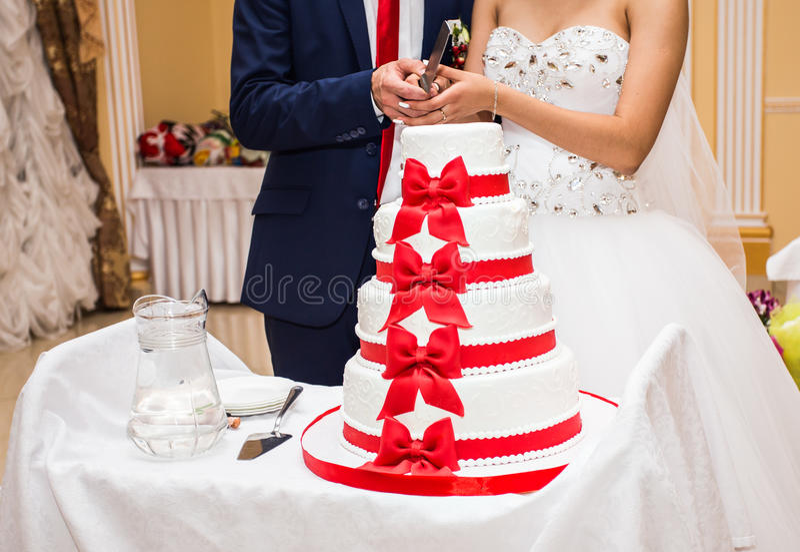 De schoonheidsbruid en de knappe bruidegom snijden een huwelijkscake stock afbeelding