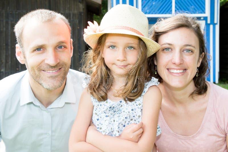 De schoonheidsdochter in de zomer van de strohoed het stellen met mooie moeder en de knappe vader in huis tuinieren stock fotografie