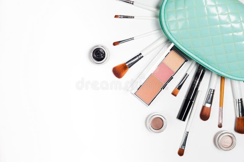 De schoonheidsmiddelen wordt uitgegoten van een kosmetische zak, handtassen op een wit stock foto's
