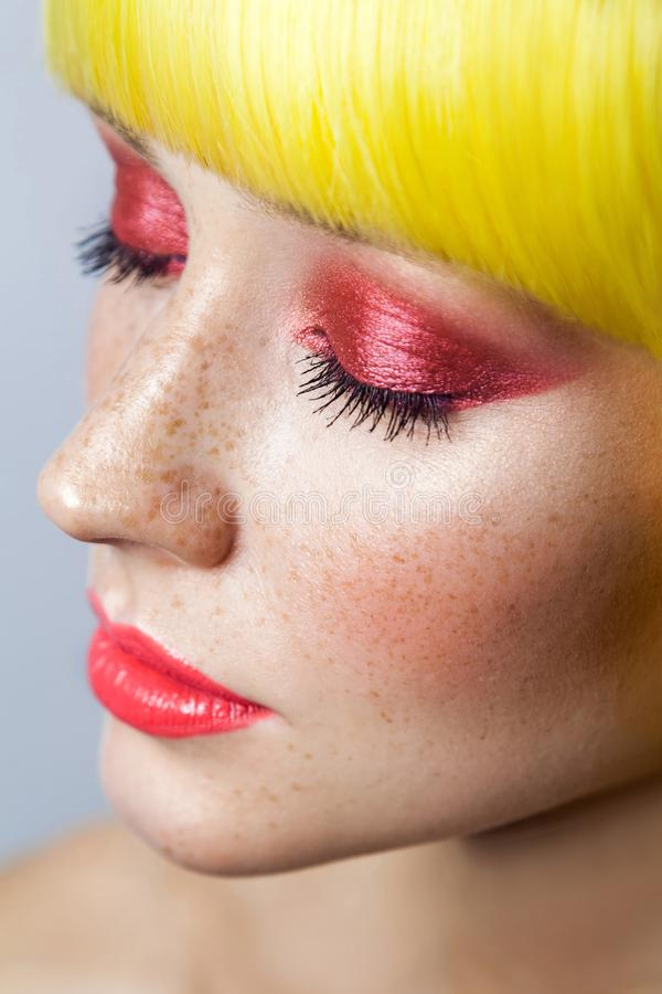 De Schoonheidsportret van de close-up sloot het hoogste mening van leuk jong kalm vrouwelijk model met sproeten, rode make-up en  stock afbeeldingen
