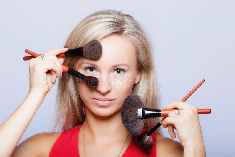 De schoonheidsprocedures, vrouw houdt samenstellingsborstels dichtbij gezicht. stock afbeelding