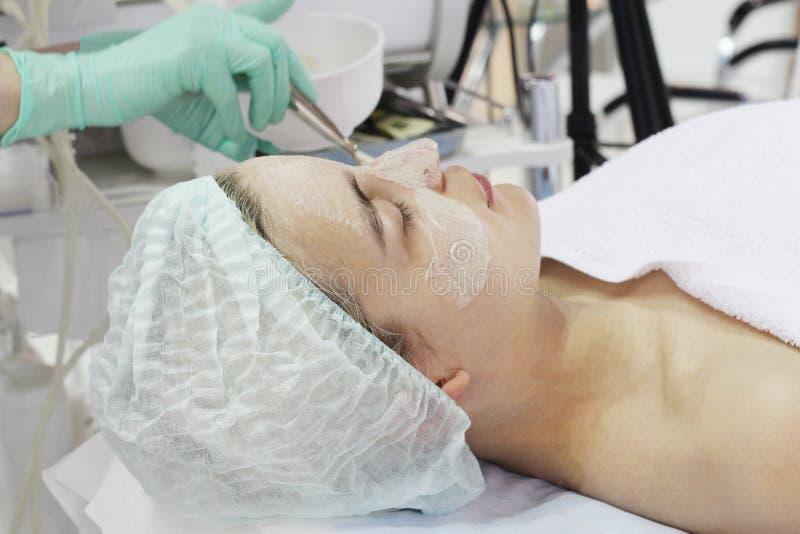 In de schoonheidssalon doet een jonge vrouw een schil op haar gezicht royalty-vrije stock afbeeldingen