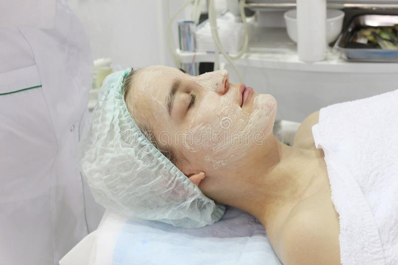 In de schoonheidssalon doet een jonge vrouw een schil op haar gezicht royalty-vrije stock afbeelding