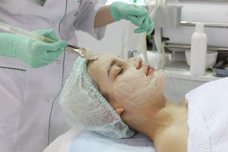 In de schoonheidssalon doet een jonge vrouw een schil op haar gezicht stock fotografie