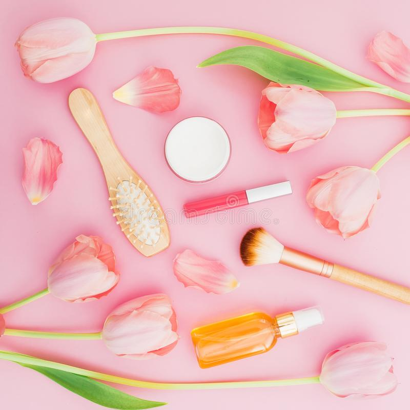 De schoonheidssamenstelling met tulpen bloeit en make-up vrouwelijke schoonheidsmiddel, aroma en kam op roze achtergrond Hoogste  royalty-vrije stock afbeeldingen