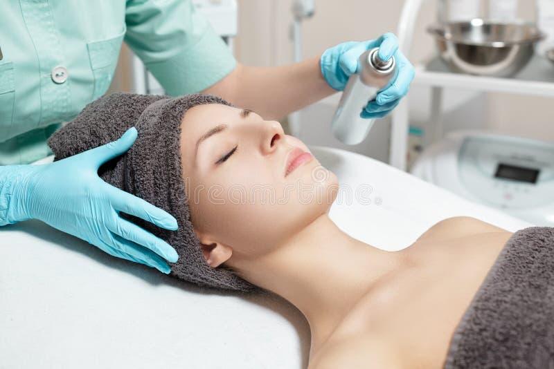 de schoonheidsspecialist gebruikt gezichtsnevel in Kuuroordsalon de kosmetische zorg van de procedurehuid royalty-vrije stock afbeelding