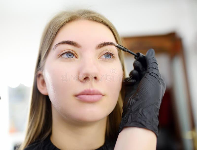 De schoonheidsspecialist kamt wenkbrauwen gebruikend speciale borstel op gezichts jong mooi model De gezichtszorg en maakt omhoog royalty-vrije stock foto
