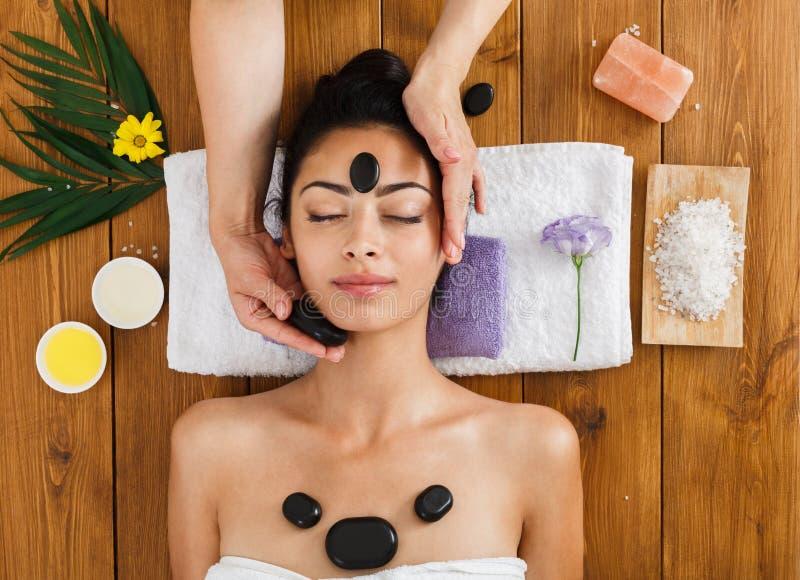 De schoonheidsspecialist maakt stone massage spa voor vrouw op wellnesscentrum royalty-vrije stock fotografie