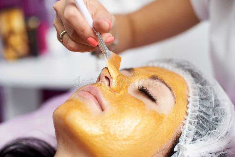 De schoonheidsspecialist met speciale borstel zet op het gouden masker van het gezichtsmeisje stock foto's