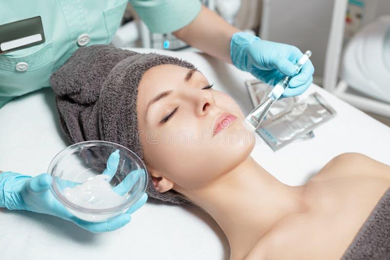 De schoonheidsspecialist past gezichtsmasker met borstel op mooie jonge vrouw in Kuuroordsalon toe de kosmetische zorg van de pro stock foto's