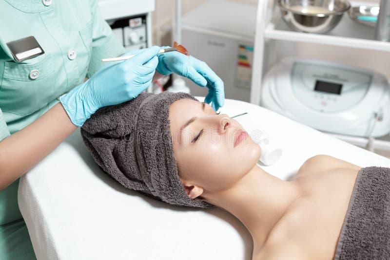 De schoonheidsspecialist past gezichtsmasker met borstel op mooie jonge vrouw in Kuuroordsalon toe de kosmetische zorg van de pro stock afbeeldingen