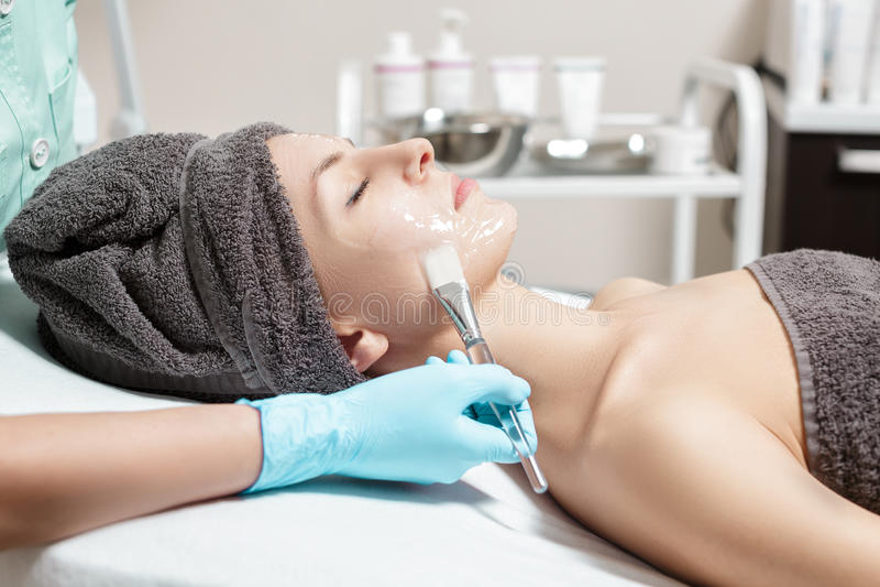 De schoonheidsspecialist past gezichtsmasker met borstel op mooie jonge vrouw in Kuuroordsalon toe de kosmetische zorg van de pro royalty-vrije stock foto