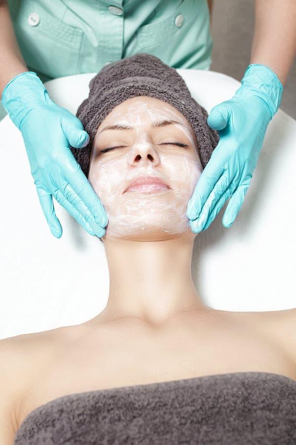 De schoonheidsspecialist past gezichtsmasker op mooie jonge vrouw in Kuuroordsalon toe de kosmetische zorg van de procedurehuid M stock foto