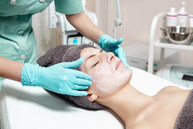 De schoonheidsspecialist past gezichtsmasker op mooie jonge vrouw in Kuuroordsalon toe de kosmetische zorg van de procedurehuid M royalty-vrije stock fotografie