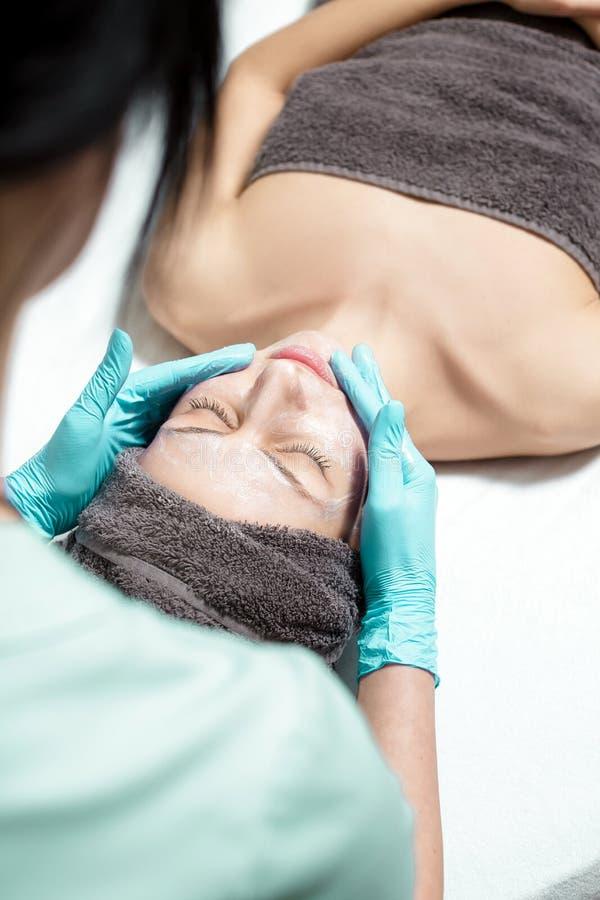 De schoonheidsspecialist past gezichtsmasker op mooie jonge vrouw in Kuuroordsalon toe de kosmetische zorg van de procedurehuid M royalty-vrije stock afbeelding