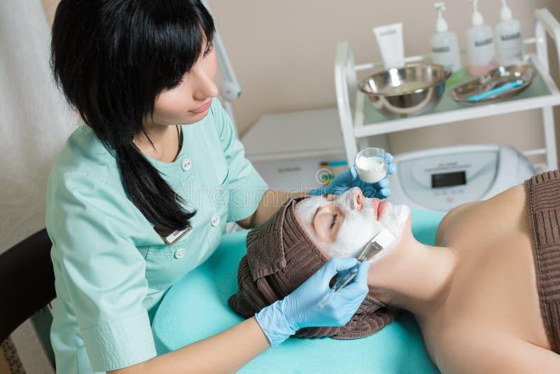 De schoonheidsspecialist past gezichtsmasker op mooie jonge vrouw in Kuuroordsalon toe de kosmetische zorg van de procedurehuid M stock afbeeldingen