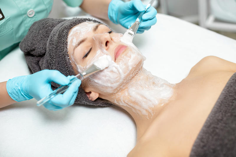 De schoonheidsspecialist past gezichtsmasker op mooie jonge vrouw in Kuuroordsalon toe de kosmetische zorg van de procedurehuid M stock afbeelding