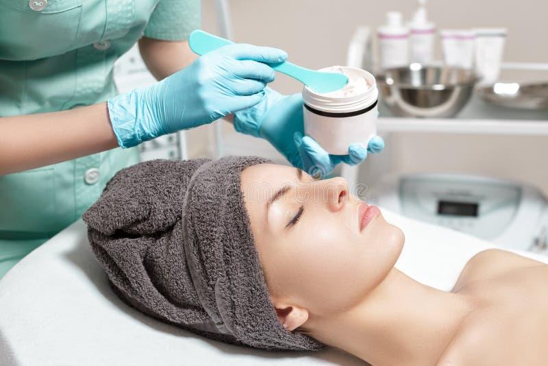 De schoonheidsspecialist past gezichtsroom op mooie jonge vrouw in Kuuroordsalon toe de kosmetische zorg van de procedurehuid stock afbeeldingen